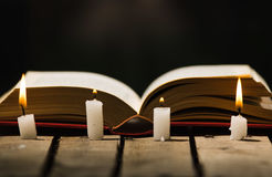 Thick book lying open on wooden surface, wax candles placed in front, beautiful night light setting, magic concept shoot Royalty Free Stock Photography