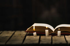 Thick book lying open on wooden surface, wax candles placed in front, beautiful night light setting, magic concept shoot Stock Photo