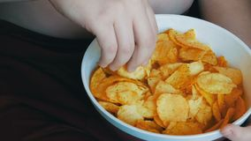 Thick boy boy eating potato chips. Folds of fat on abdomen of the child. Unhealthy food, fast food. Thick boy boy eating potato chips. Folds of fat on the stock footage