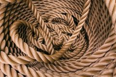 Thick brown rope rolled into a roll stock photography