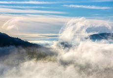 Thick cloud formation rising from the valley. Thick cloud formation rising from the forests in valley. dramatic view of nature process in mountains at autumn Royalty Free Stock Images