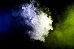 Background from the smoke of vape. Thick colorful smoke of green and blue on a black isolated background. Background from the smoke of vape Royalty Free Stock Photos