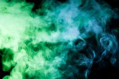 Background from the smoke of vape. Thick colorful smoke of green, blue on a black isolated background. Background from the smoke of vape Royalty Free Stock Photography
