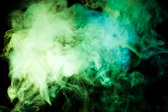 Background from the smoke of vape. Thick colorful smoke of green, blue on a black isolated background. Background from the smoke of vape Stock Photography