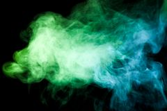 Background from the smoke of vape. Thick colorful smoke of green, blue on a black isolated background. Background from the smoke of vape Stock Photo