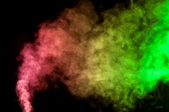 Thick colorful smoke. Of green, red, yellow on a black isolated background. Background from the smoke of vape Stock Photos