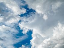Thick cumulus clouds with a deep blue sky making their way through royalty free stock images