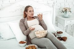 Thick expectant woman in pastel outfit lying in bed and carrying donut. Bunch of food. Thick expectant woman in pastel outfit lying in bed and carrying donut royalty free stock photography