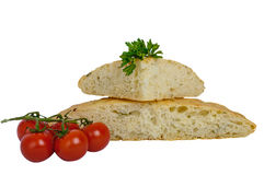 A thick flat cake - pita bread with greens and cherry tomatoes on a branch isolated on white background. Stock Photos