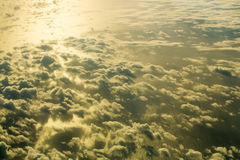 Thick fluffy clouds on sky over sea. Thick fluffy clouds on sky over grey and green idyllic sea or ocean water surface background. Upper layers of atmosphere Royalty Free Stock Image