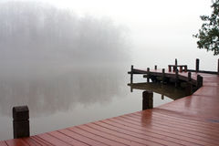 Thick Fog Covers Wooden Dock And Lake On Winter Day. Fog covers a lake and wooden deck on a dreary winter day royalty free stock photo