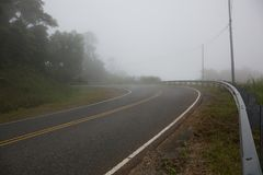 Thick Fog over Curved Road Makes Driving Conditions Dangerous Royalty Free Stock Image