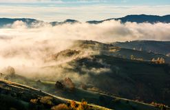 Thick fog over the rolling hill in autumn Stock Photo