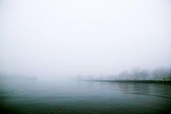 Thick Fog over Water. A river edge in thick fog during the winter Stock Photo