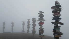 Thick fog and strong wind on mount Mashuk. Famous observation deck with distance signs to different cities of the world. stock footage