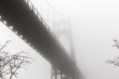 St. John`s Bridge in a Foggy Winter Day at Cathedral Park. Thick fog surrounds St. John`s Bridge in Portland, Oregon, USA Stock Image