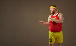 Thick funny man in sports clothes points with his finger. royalty free stock image