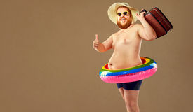 Thick funny man in swimming trunks wearing a hat and crocheted o Stock Image