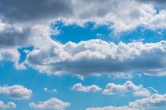 Thick gray clouds in the blue sky on a sunny day. Natural background stock image