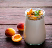 Thick Greek yogurt with granola, peaches and mint Royalty Free Stock Photography