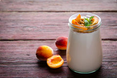 Thick Greek yogurt with granola, peaches and mint Stock Photography