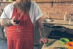 Thick guy drinking wine while cooking. Happy fat man is enjoying alcohol beverage during food preparation. He is standing in kitchen and holding wineglass Royalty Free Stock Image