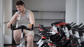 Thick guy practices on an exercise bike, stopping to eat pizza and continues to train stock video