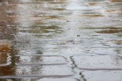 Raindrops Splattering on Pool Deck Tiles. Thick, heavy raindrops splatter on the tiles of a pool deck in a warm, humid afternoon in late June in Florida Stock Image