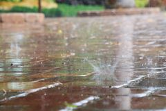 Raindrops Splattering on Pool Deck Tiles. Thick, heavy raindrops splatter on the tiles of a pool deck in a warm, humid afternoon in late June in Florida Stock Photo