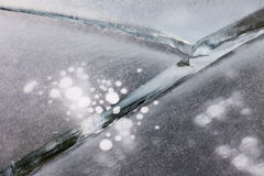 Thick ice cracked with round air bubbles abstract Stock Images