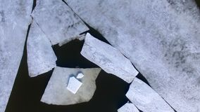 Thick ice slabs lying over murky river waters. stock video