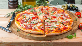 Thick italian pizza. With salami on a wooden tray Royalty Free Stock Photos