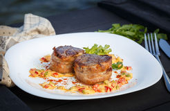 Thick juicy fillet steak medallions grilled to perfection. And served with vegetables on white plate Stock Image