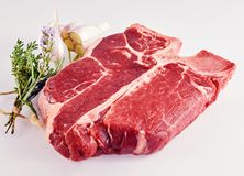 Thick juicy raw porterhouse steak with herbs. Thick juicy raw porterhouse steak with assorted herbs tied in a bouquet garni and sliced through garlic cloves on a Stock Photo