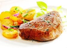 Thick juicy steak with crisp roast potatoes Royalty Free Stock Image
