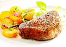 Thick juicy steak with crisp roast potatoes Royalty Free Stock Image