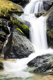 Thick mellow powerful waterfall between stones Royalty Free Stock Photography