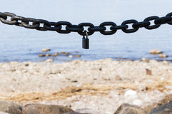 Thick metal chain with a lock on sea background Stock Photography