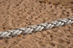 Thick natural rope on the background of sand royalty free stock image