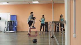 Thick obese guy together with personal slim coach do physical jerks in gym. Overweight male and female trainer with. Fat man training with woman instructor and stock footage