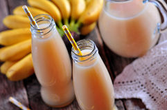 Thick organic banana juice in bottles with straws on an old table. Royalty Free Stock Photo