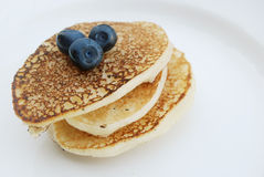 Thick pancakes with fresh berries. Russian thick pancakes on a white plate close-up with fresh blueberries Stock Photos