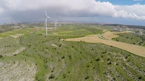 Thick rainy clouds over green landscape and wind farm, weather change forecast. Stock footage stock video