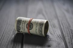 A thick roll of hundred dollar banknotes tied a red rubber band lies on the grey wood table stock photos
