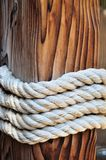 Thick rope around a wooden mooring bollard, Croatia Royalty Free Stock Image