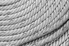 Thick rope gray braided weathered old folded in a circle piece parallel lines rigid base marine design stock photo