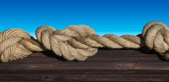 Thick rope with knots. On old blackboard on blue background royalty free stock images