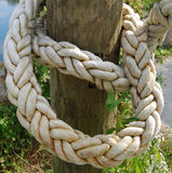 Thick rope post. Thick, heavy rope or hawser wrapped around a wooden post or bollard Stock Photography