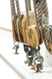 Thick rope and pulley of sailing ship. Details of an old sailing ship. Thick ropes going through the timber pulleys which are attached to ship hull with metal stock photos