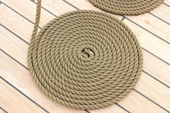 Thick rope wrapped in spiral lying on deck of ship Stock Images